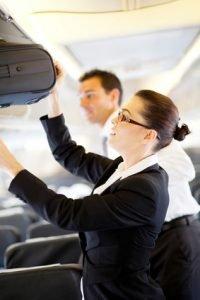 flight attendant helping passenger with luggage